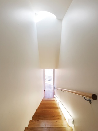 A curved bulkhead occupies the stairwell, with a porthole skylight admitting natural light.
