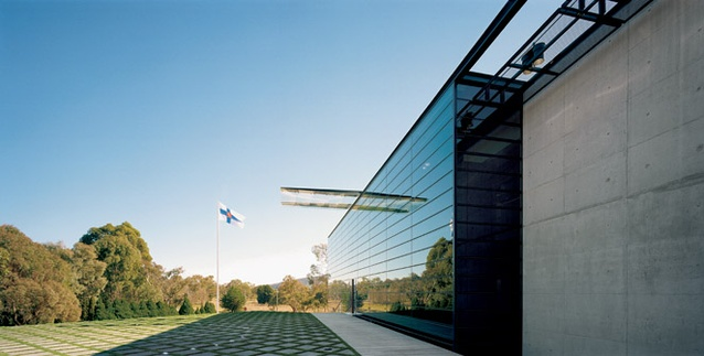 The glazed reflective wall, glass canopy and formal landscaping of the entry.