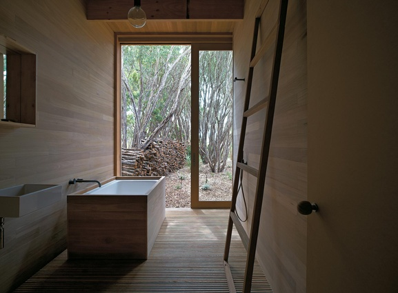 Simple fittings and timber panelling give Japanese aesthetic to this bathroom from Pirates Bay House by O'Connor and Houle Architecture.