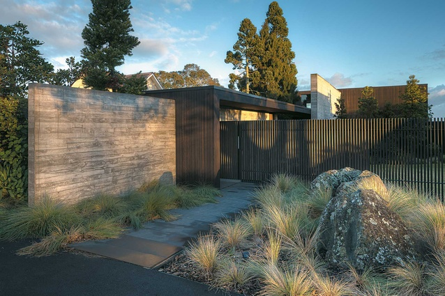 The vertical fins of the fence allow discreet glimpses of the house.