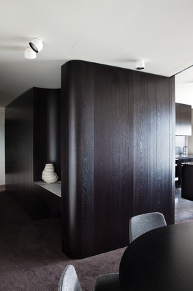 Dark-stained, oak-panelled walls define the various zones within the apartment.
