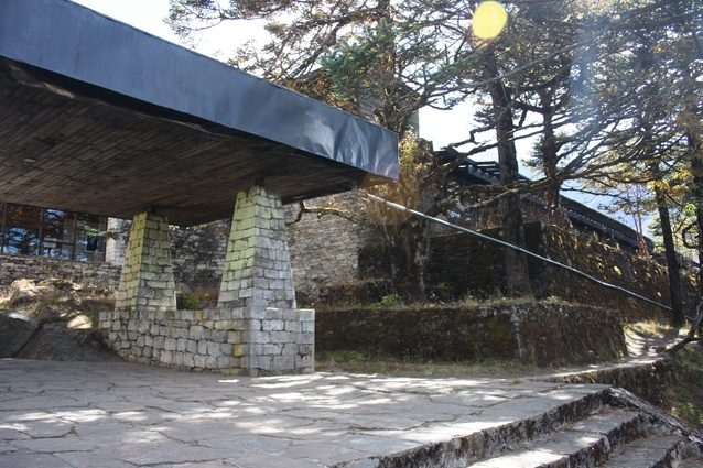 A low lying horizontal form in the spirit of Wright with flat roof, stone paved terrace and buttress-like columns.