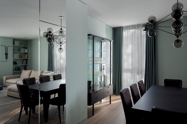 A Roll & Hill Modo chandelier with black smoke glass pendants hangs above the dining table.