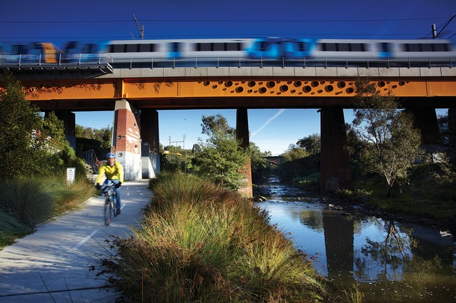The rail bridge runs above the Merri Creek and the cycling path.