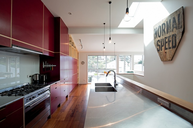 The striking red galley-style kitchen has a staircase behind the bench, with built-in shelving. This enables an open-plan, light-filled living and dining area with views onto the garden.