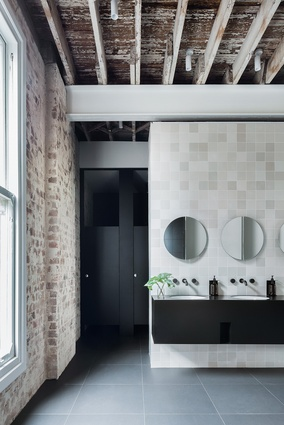 The tiled walls of the bathrooms sympathetically reference the colour in the brickwork.