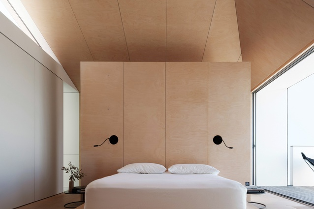 The main bedroom enjoys ocean views and has a ceiling that folds up like an origami ply-clad vault.