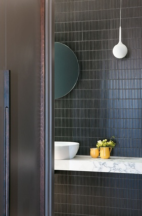 Dark vertical tiles combine with a solid benchtop in this bathroom. Airlie Bank house by Neometro with McAllister Alcock Architects.