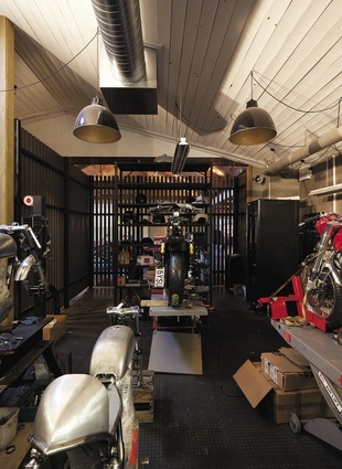 The custom motorcycle workshop is discreetly positioned behind slatted timber battens.