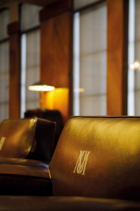 Detail of the original boardroom chairs with MU logo.