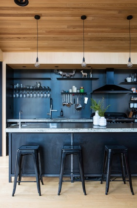 In this Kawau Island holiday home, steel shelving on the splashback lifts items off the benchtop and allows quick access to utensils and everyday pantry items.