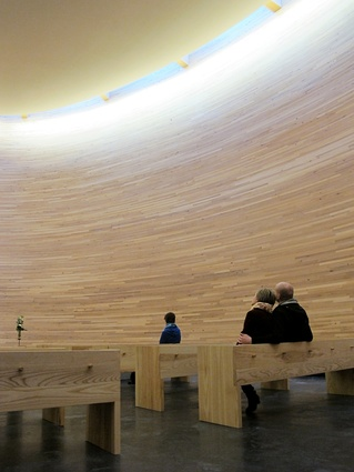 Birch-lined walls envelope the chapel interior in a cone of silence.