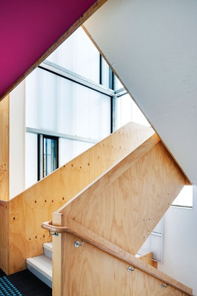 Women's Health and Family Services. The light-filled stairwell and its luminous colours connect the vertical spaces of the new block with the cottages.