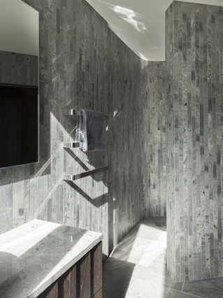 Rather than seeking a predetermined pattern, the bathroom tiling becomes enticing due to its randomness. The curvature of a wall separates the basin from the shower area.