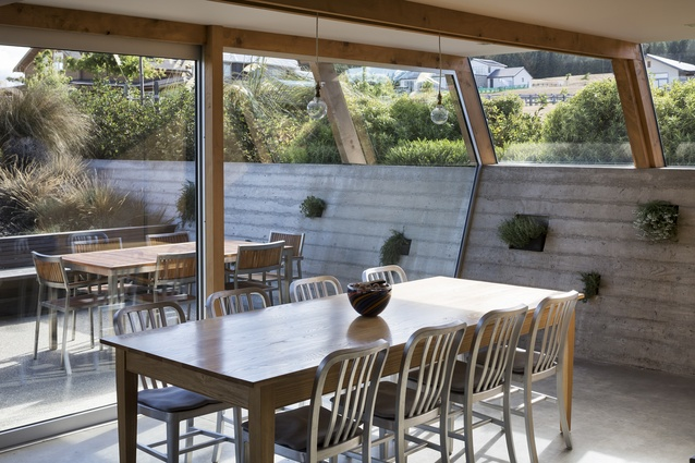 The dining room of Wanaka House. The in-situ concrete wall offers a practical thermal mass element to regulate temperatures.