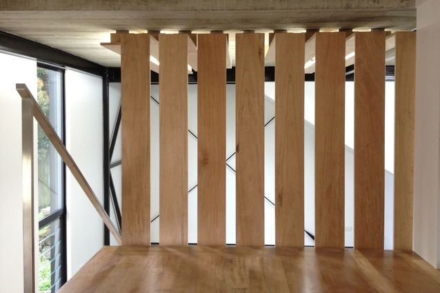 Band-sawn formwork cast into the concrete ceilings is juxtaposed against the suspended timber Rosawa boards, which act to direct and hide the light sources throughout.