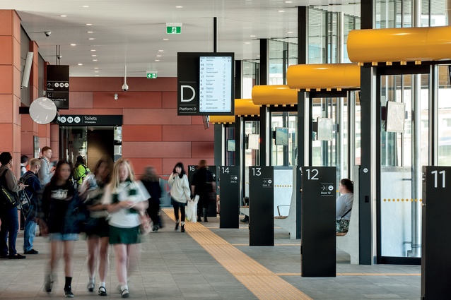 """Users gather in a central space with a number of bus bays arrayed in front of them with clear signage."""