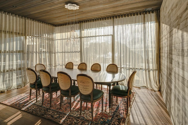 The dining room with light pouring in through the lightly screened floor-to-ceiling glazing.