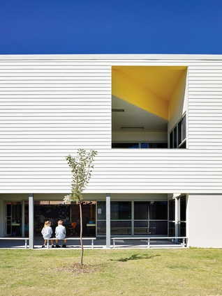 Apertures on the upper level provide glimpses into brightly coloured, double-height outdoor rooms.