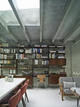 The interior's white resin floors and concrete walls and ceiling are softened in the dining area by the inclusion of Kai Kristiansen's rosewood shelving system.