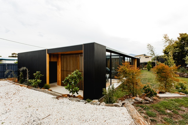 A black shell envelops the timber interiors of the Five Yards house.
