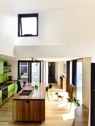 A small, high window infuses controlled northern light into the kitchen below.