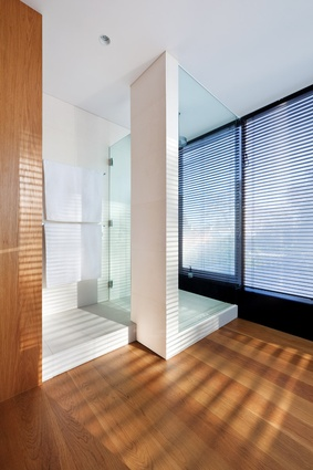 A simple palette of materials flows into the upper-level bathroom.