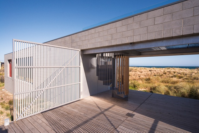 A timber entry deck at the Churchill House splits two pavilions and opens to a view of dunes and ocean.