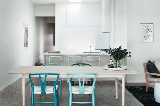 The white kitchen is a plain and fresh backdrop for subtle colour in the ash table, marble benchtop and Wishbone chairs. Prahran Residence by Wonder.