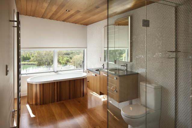 Te Hīnaki House. This timeless bathroom draws on the timber theme of the rest of the house, with the addition of white hexagonal tiling.
