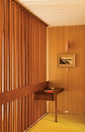 A timber-screened passage outside the upper-level bedrooms overlooks the hall below.