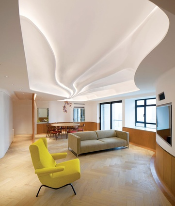 A swooping form conceals exposed concrete beams at the ceiling-edge perimeter of the living space.