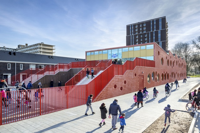 IKC Zeven Zeeën, Amsterdam. The entrance of the superstructure is via a large, bright outdoor staircase, and the red concrete facade and round windows add a playful element.