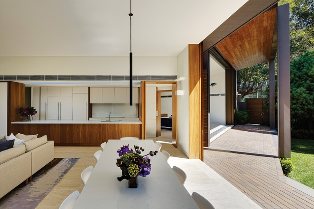 An internal material palette of blackbutt timber, white plaster walls and travertine floors contrasts with the dark masonry exterior.