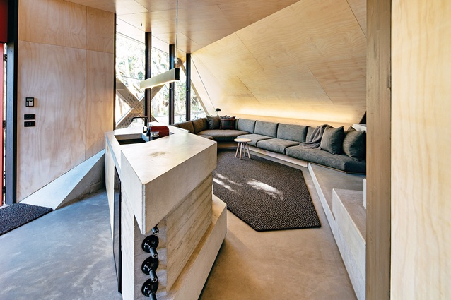 A seating nook is tucked into the ceiling's lowest point, where the sloped roof meets the ground.