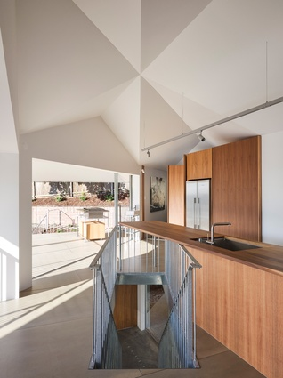 A dramatic faceted whitewashed plywood ceiling at the intersection of the two main volumes is a major feature of the living space.