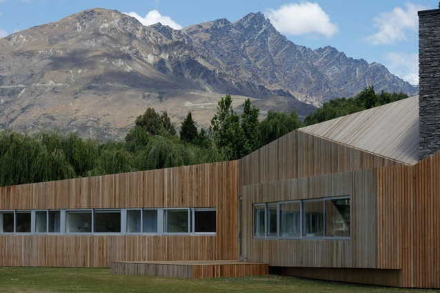 The cedar-clad house unfolds in front of the mountains.