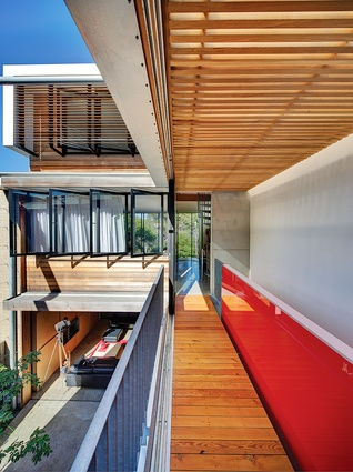 Doors slide back to turn a bridge between bedrooms into a balcony to the courtyard.