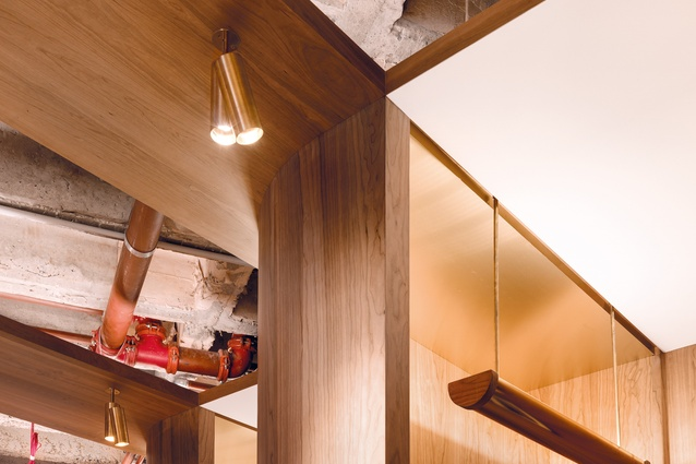 A three-dimensional feature ceiling of timber and brass links the individual elements within the office.