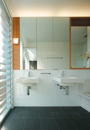 High gloss wall tiles and charcoal floor tiles keep the bathroom clean and minimal.