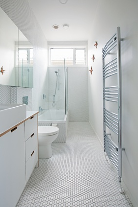 The all-white bathroom features hexagonally tiled flooring and a bespoke ply-edged vanity.