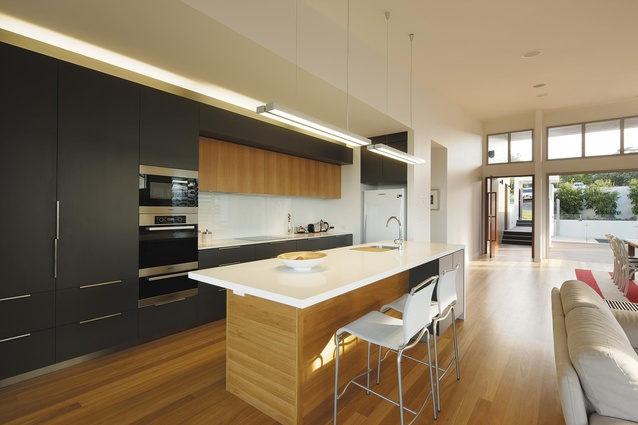The kitchen of the Queensland home is sleek, yet warm, thanks to the use of wood.