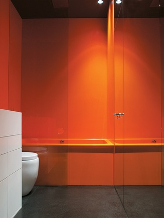 Bright orange Corian with a custom thermoformed bath creates a striking bathroom by Thomas Jacobsen.