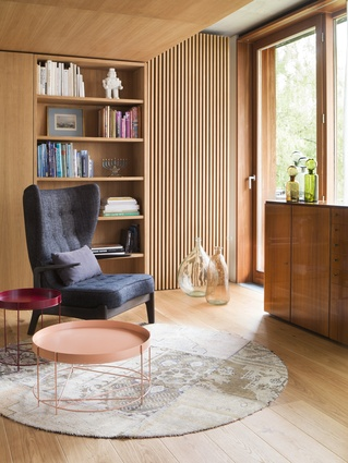 Pale, honey-coloured timber envelops this apartment, with texture provided through panelling and in-built shelving.
