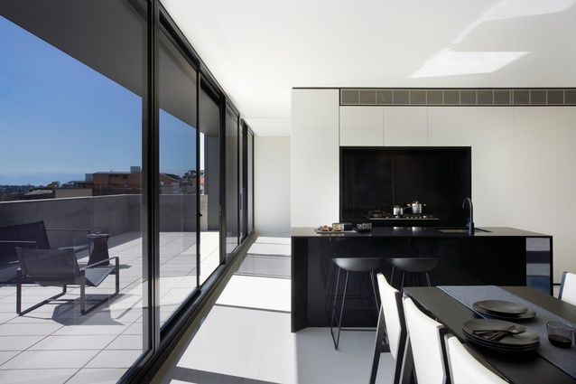 Set back behind the brick membrane, a glass plane integrates operable glazed doors and windows.