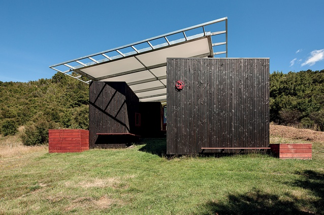 A flying roof appears to float over a collection of small buildings, creating flexible spaces in between.