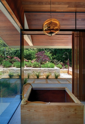 A bathhouse on the ground floor features a Japanese timber tub and is open to views of the garden.
