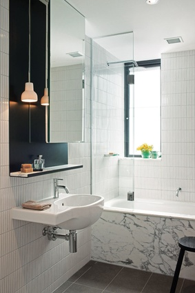 The bathrooms feature Japanese finger tiles laid vertically on end and a black steel vanity.