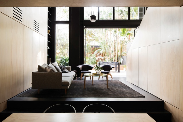 On the lowest level of House Elysium, large windows face west onto a garden, with a discreet studio/garage tucked into the end.