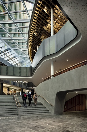 """Rugged – """"student-proof"""" – materials that permeate through the atrium spaces include gently curving black steel and concrete work."""